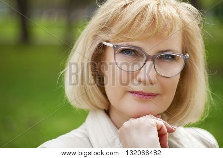 Close up portrait of lovely middle aged woman in the summer park