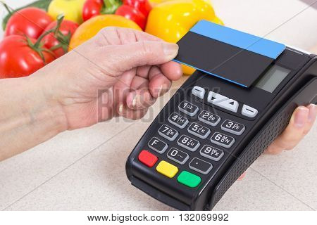 Hand of elderly senior woman using payment terminal with contactless credit card cashless paying for shopping fruits and vegetables