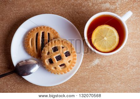 Cup of tea and lemon, cookies with jam in saucer on table top view.