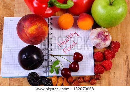 Fresh fruits and vegetables with notebook for writing notes concept of slimming diet and healthy nutrition