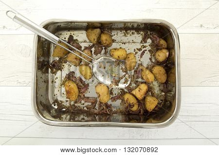 Mustard-crusted new potatoes with shallots in a dish with serving spoon on a rustic wooden table