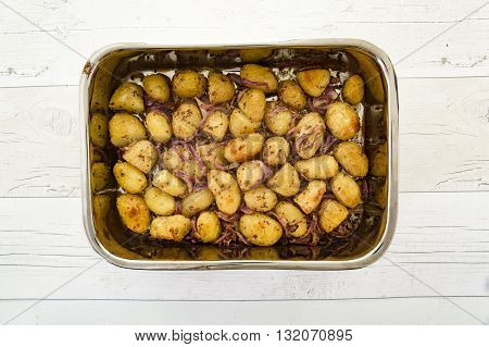 Mustard-crusted new potatoes with shallots in a dish on a rustic wooden table