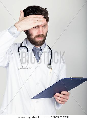close-up portret of a Doctor holding a map-case for note, stethoscope around his neck. He wipes his forehead. different emotions.