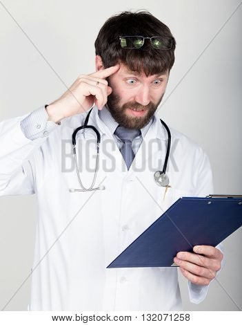 close-up portret of a Doctor holding a map-case for note, stethoscope around his neck. He twists his index finger at his temple. different emotions.