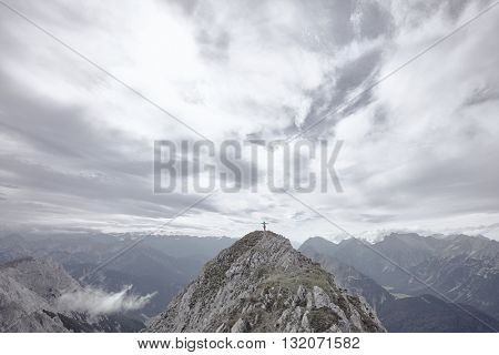 Woman wearing outdoor clothing, climbing harness and helmet, standing on top of mountain with arms outstretched, celebrating successful ascent and enjoying view to valley and peaks - freedom concept