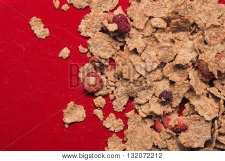 Muesli with fruits on a red plate