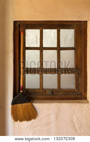 Old styled broom stick hanging by the wooden vintage window close to the entrance door to keep away bad folks and spirits
