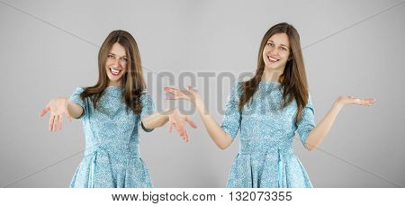 Happy beautiful young women in a turquoise dress on a gray background. Studio portrait
