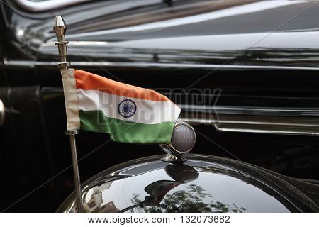 The tricolor Indian flag set on a very old black vintage car.