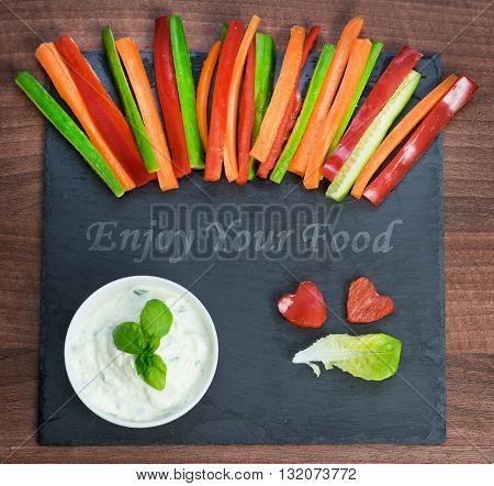 Colorful vegetable sticks with a spicy dip on a slate plate with the top view