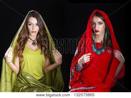 Young beautiful brunette women in green and red indian dress, isolated on black background