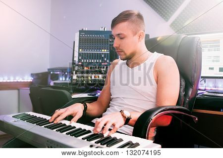 DJ plays piano music in the sound recording studio interior. Process of studio recording of club music.  Young male composer plays new music track on electronic  piano.