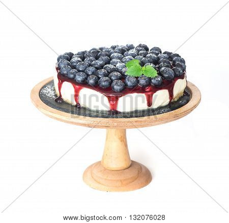 Cheesecake with a jam and blueberry on wooden stand isolated on white background