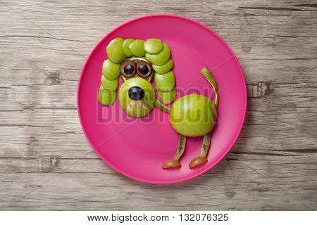 Poodle made of fresh fruits on plate and wood