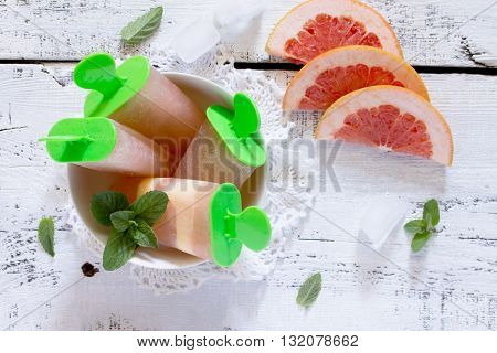Delicious Fruit Ice With A Grapefruit On A White Wooden Background. Top View .