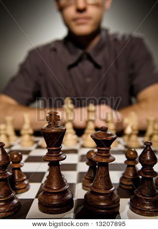 Chess master thinking before making a move (shallow Dof, focus on front chess piece)