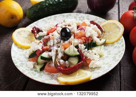 Shopska salad with cheese, olives, cucumber, tomato and chili peppers