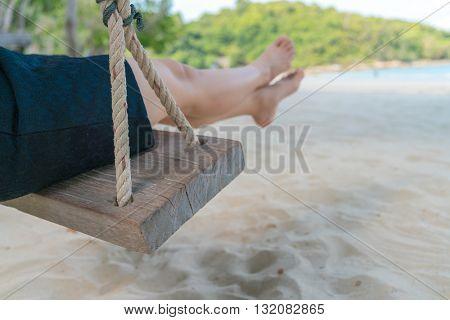 Woman leg on a swing at tropical sea beach