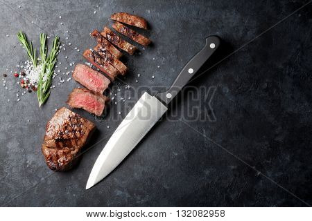 Grilled sliced beef steak on stone table. Top view with copy space