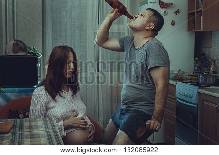 Sad pregnant wife and next drink alcohol husband. Social problems of the family.