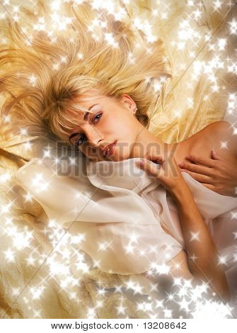 Beautiful blond girl lying on a  golden fabric