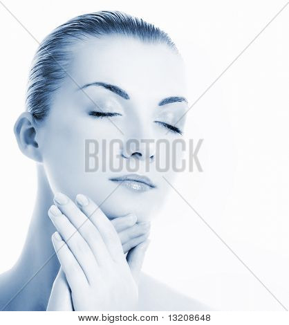 Beautiful young woman massaging her face (toned in blue)