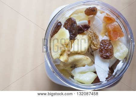 Plastic jar with mixed dried fruit over wooden surface. Selective focus. High angle view