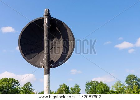 the old round road sign is located the back closeup on a rack from a pipe and separately against the sky