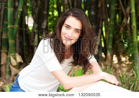 Smiling Young Woman In Front Of Bamboo Trees