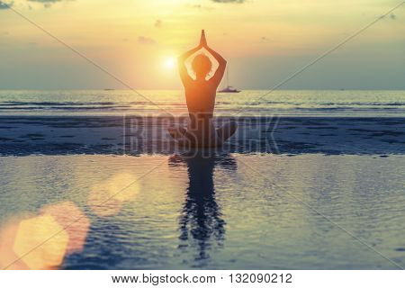 Silhouette woman practicing yoga at seashore during sunset. Health, meditation and tranquility.