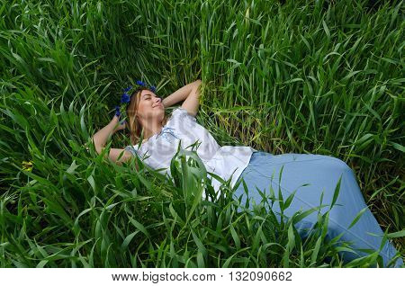 Beautiful girl lies in the field among green ears of wheat