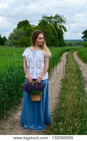 Beautiful young woman stands with basket of wild flowers on rural road