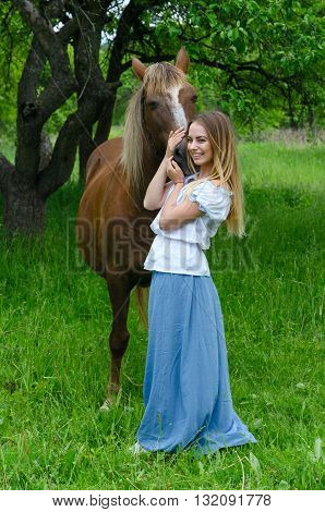 Beautiful smiling girl with long blond hair embraces bay horse in apple orchard