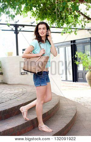 Beautiful Woman Walking Down Steps Talking On Cellphone