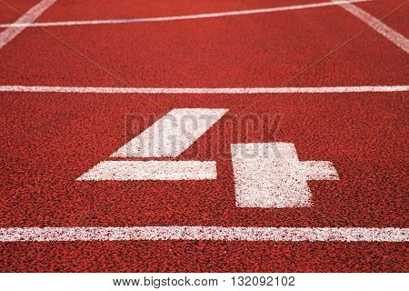 Number Four. White Track Number On Red Rubber Racetrack, Texture Of Racetracks In Stadium
