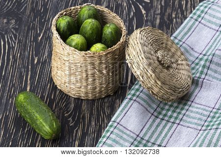 Fresh cucumbers in basket on the wooden desk