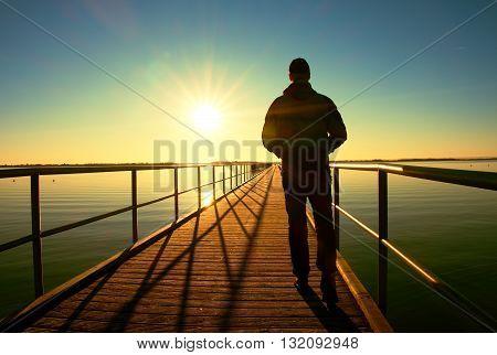 Man Silhouette Walk On Wharf Construction Above Sea To Sun. Fantastic Morning.