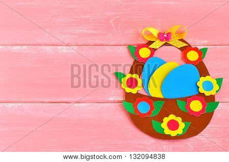 Easter basket with eggs and flowers made of cardboard, on pink wooden background, with space for congratulation to Easter. Fun Easter craft Idea for kids
