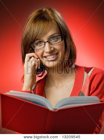 Beautiful redhead woman searching a phone number in telephone directory