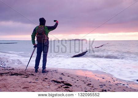Man With Poles Above Head. Tourist In Green Clothing And Backpack With Hands In The Air Along Beach.