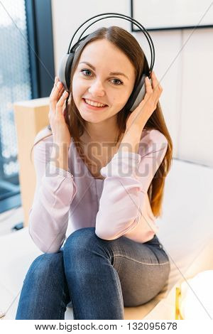 Attractive young student listening to music in library language courses the learning process gadgets