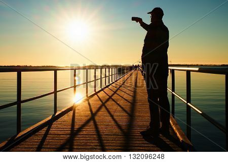 Man On Pier Photograph Morning Sea. Tourist With Smart Phone In Hand. Fantastic Morning