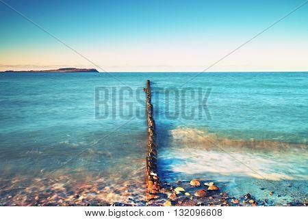 Wooden breakwater on wavy Baltic Sea, stony beach
