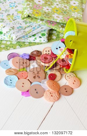 Pieces of cloth with flower pattern, mixed colors group of buttons. Needlework concept