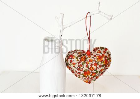 Composition for Valentine's day - fabric heart, white vase, white painted branch. Valentine's day idea home decor