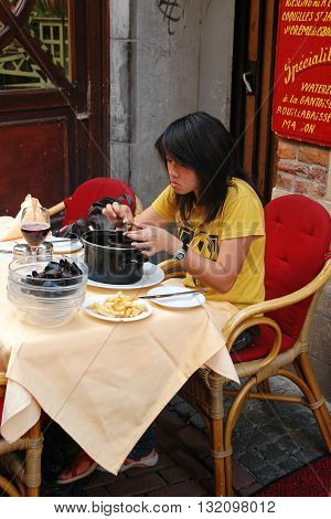 BRUSSELS, BELGIUM, AUGUST 31, 2005: An unidentified woman opens and eats clam