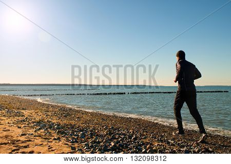 Tall Man In Dark Sportswer Running And Exercising On Stony Beach At Breakwater.