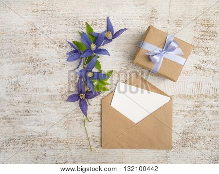 Gift box wrapped in brown kraft paper with violet satin bow blue flowers and envelope with greeting card on the wooden painted board