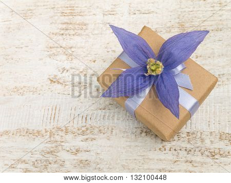 Gift box wrapped in brown kraft paper with satin ribbon and violet four petals flower on the white wooden painted board
