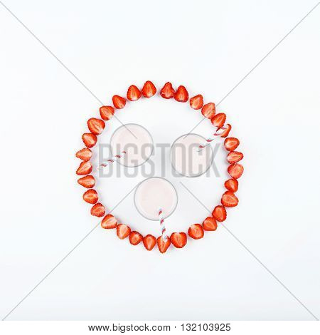 Strawberry smoothies on a white background with strawberry slices. Top view. Flat lay